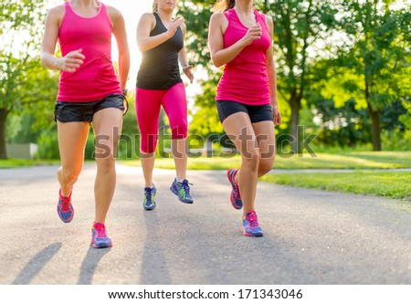 group of healthy girls running outdoors at sunset with lens flare. - stock photo