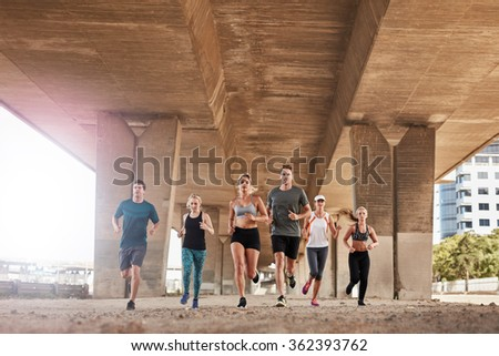 Group of healthy people running under a bridge. They are running in the city wearing sport clothing. - stock photo