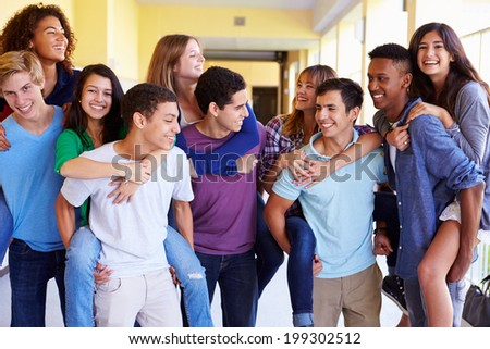 Group Of High School Students Giving Piggybacks In Corridor