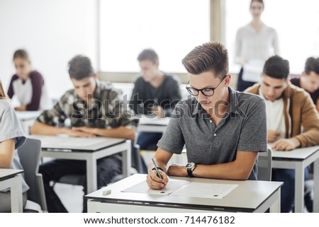 Group of high school students having test at classroom.