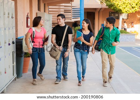 Group of high school students talking and laughing in a hallway between classes - stock photo