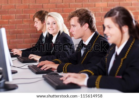 group of high school students using computers in classroom