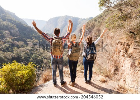 group of hikers arms open on top of the mountain - stock photo