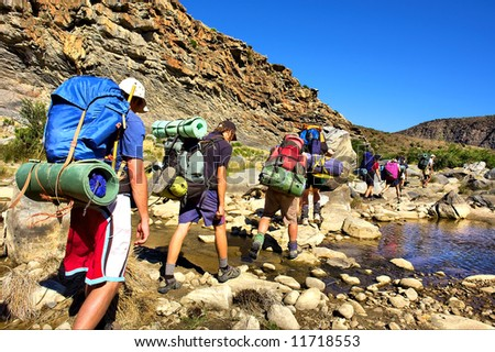 Group of hikers crosses small river in mountains. Shot in the Langeberge highlands near Grootrivier and Gouritsrivier rivers crossing, Garden Route, Western Cape, South Africa. - stock photo