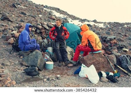 Group of hikers in the mountain. climbers in the camp near the tent. mountaineering - stock photo