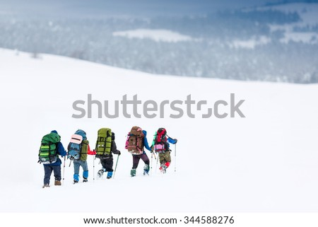 group of hikers in winter mountains