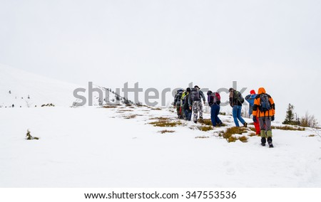 Group of hikers in winter mountains. People on winter hike in mountains, backpackers walking on snow. 28.02.2014 Carpathians, Ukraine