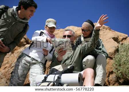 Group of hikers observing a plan - stock photo