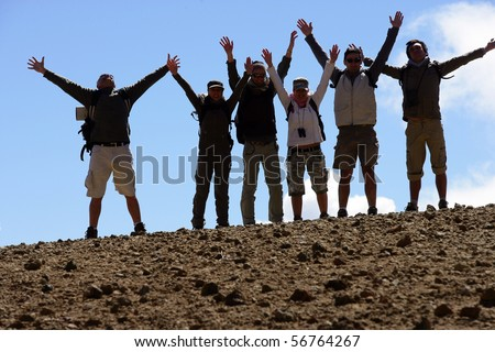 Group of hikers raising arms
