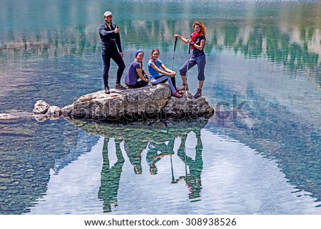 Group of Hikers relaxing on rock. Sporty Clothing People Sitting Staying on Stone in Middle of Azure Mountain Lake with Reflection of Bodies and Sky