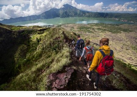 Group of hikers walking on the caldera of volcano of Batur, Bali, Indonesia - stock photo
