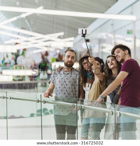 Group Of Hipsters In Shopping Mall Taking Selfie Using Smart Phone And Monopod