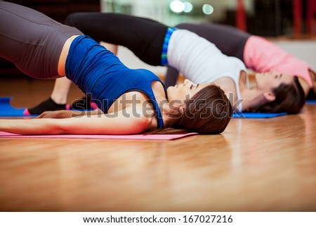 Group of Hispanic women doing crunches and working out at a gym - stock photo