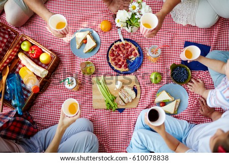 Group of humans with drinks gathered by dinner on picnic cloth