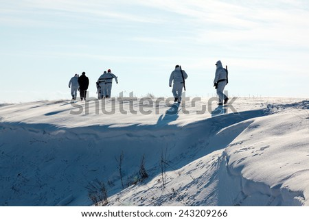 Group of hunters walking on the field in winter - stock photo