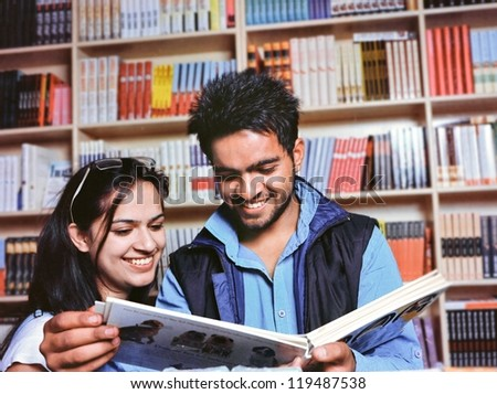 Group Of Indian Asian College Students Reading A Book In The Library