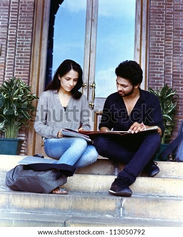 Group of Indian / asian college students sitting on stairs at the campus. - stock photo
