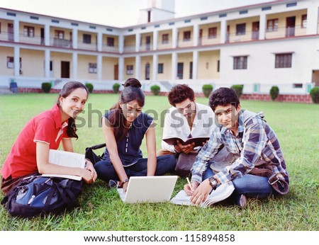 Group of Indian / Asian college students studying over the grass in the campus.