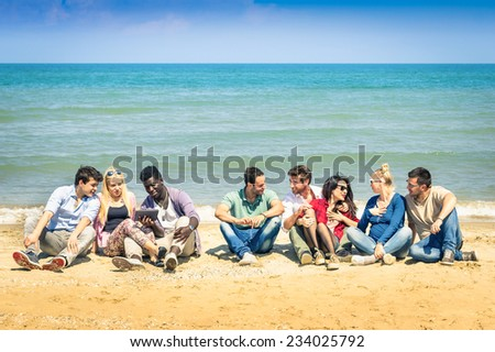 Group of international best friends sitting at beach talking with each other - Concept of multi cultural friendship against racism - Interaction with new technologies tablet and contact with nature - stock photo