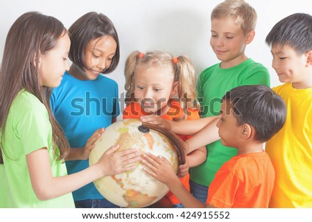 Group of international kids holding globe earth. School children learn geography.