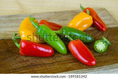 Group of Jalapeno, red and yellow  peppers on cutting board  - stock photo