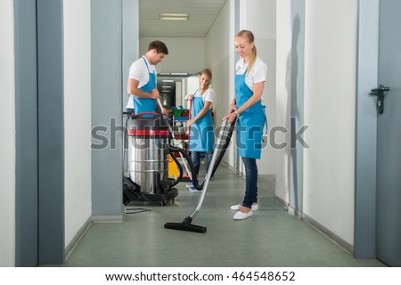Group Of Janitors Cleaning Floor In Corridor With Caution Sign