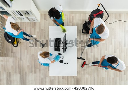 Group Of Janitors In Uniform Cleaning The Office With Cleaning Equipments - stock photo