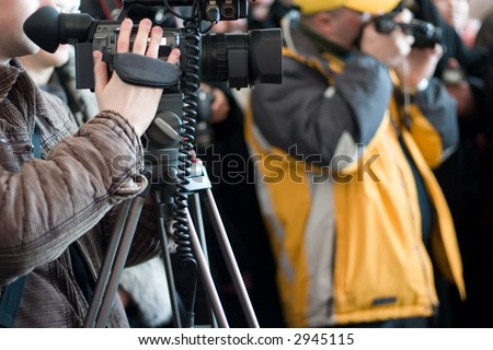 Group of journalists with photo and video cameras shooting some event - stock photo