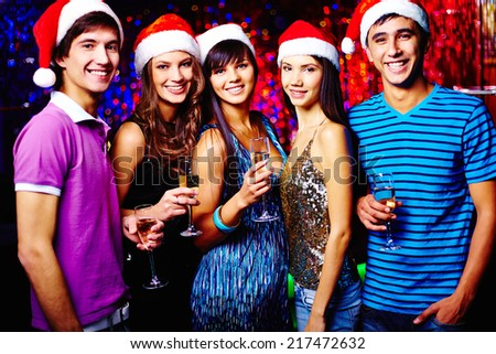 Group of joyful friends in Santa caps toasting at party - stock photo