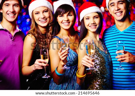 Group of joyful friends toasting with champagne at xmas party