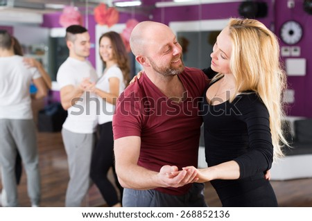 Group of joyful happy young adults dancing at dance class - stock photo