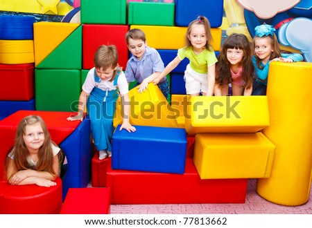 Group of joyful kids playing with large leather blocks - stock photo