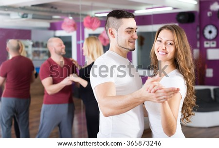 Group of joyful smiling young adults dancing salsa at dance class. Focus on guy - stock photo