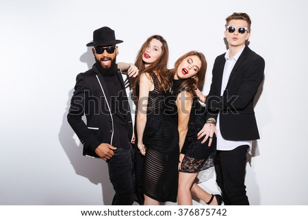 Group of joyful young friends standing and having fun over white background - stock photo