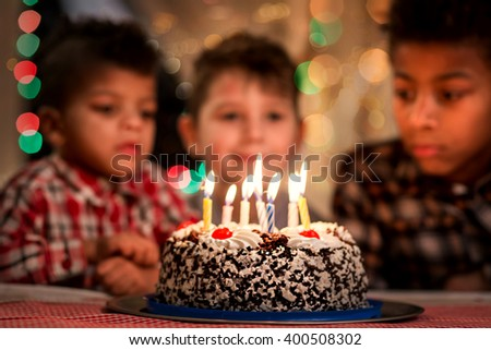 Group of kids beside cake. Boys sit near birthday cake. Our guest is here. Visiting school friend's birthday party. - stock photo