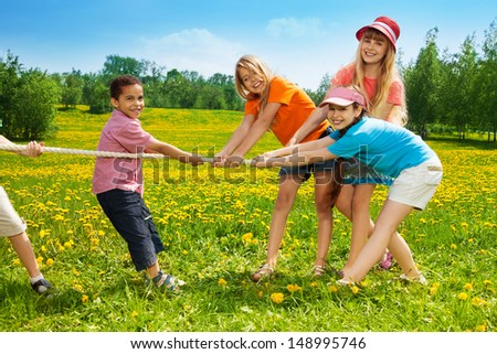 Group of kids, boys and girls playing pulling the rope in the dandelion field - stock photo
