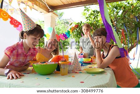 Group of kids celebrating a birthday party with a table full of food, sweets and juices in a home garden party, outdoors. Children friends eating, drinking and playing together, home exterior. - stock photo