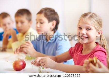 Group of kids having lunch during break with focus on smiling girl looking at camera - stock photo