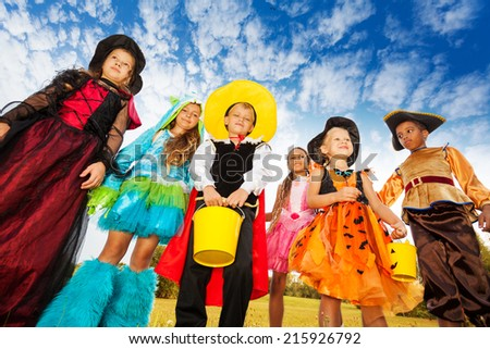 Group of kids in Halloween costumes looks down - stock photo