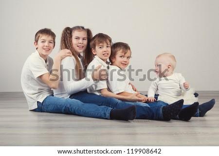 Group of kids in jeans sitting on floor, studio - stock photo