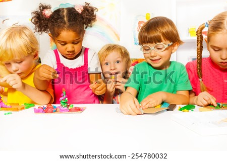 Group of kids in the kindergarten play with modeling clay in the class - stock photo
