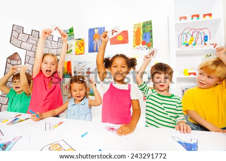 Group of kids learn first letters in reading class - stock photo