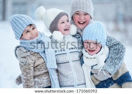 Group of kids playing in the snow in winter clear day - stock photo