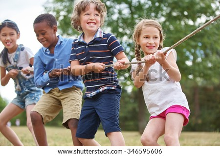Group of kids pulling a rope at the park - stock photo