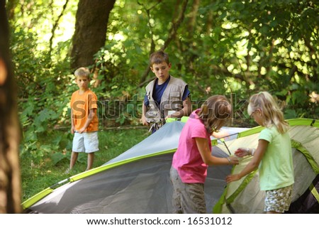 Group of kids putting together a tent - stock photo