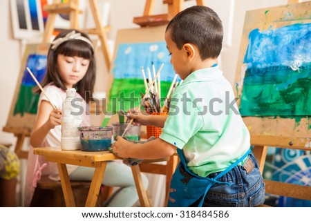 Group of kids working on a painting of a landscape during art class at school - stock photo