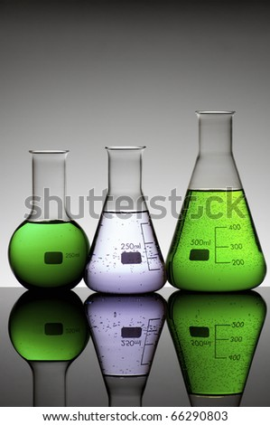 group of laboratory flasks brightly colored liquid - stock photo