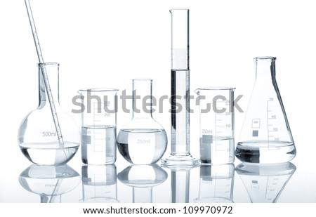 Group of laboratory flasks with a clear liquid, isolated - stock photo