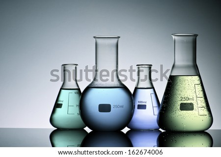 group of laboratory flasks with liquid inside - stock photo