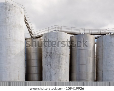 Group of large steel storage tanks at a refinery terminal used for storage and distribution of petrochemical products - stock photo